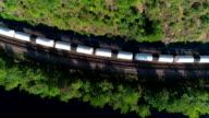 De lading trainen aan de spoorweg in de Appalachian bergen langs de rivier van de Lehigh, in de buurt van Jim Thorpe, Pennsylvania, USA. Luchtfoto beeldmateriaal.