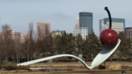The cherry on the green, located in the Minneapolis sculpture garden, with the city skyline of Minneapolis in the background