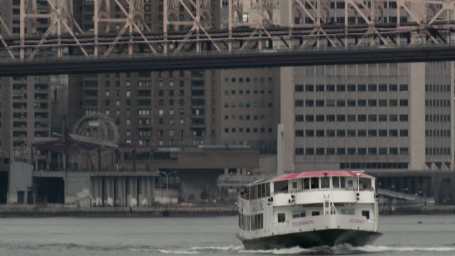 The Circle Line boat navigates the East River of Manhattan the Queensboro Bridge and the FDR Is behind