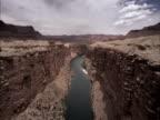 The Colorado River flows between steep rocky cliffs.