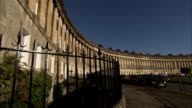 The columned facade of Royal Crescent overlooks parked cars on a street. Available in HD.