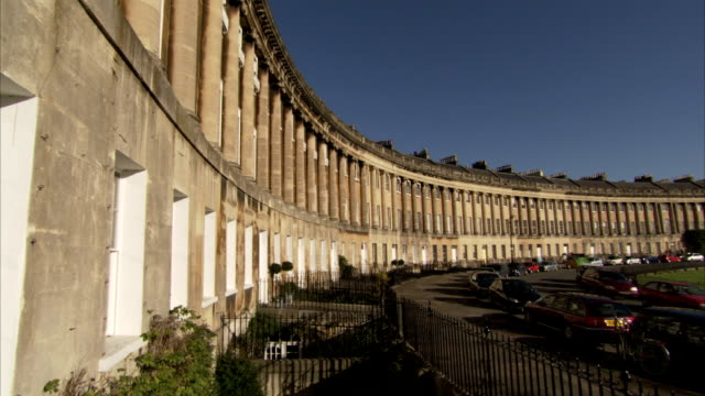 The columns on the facade of the Royal Crescent overlook parked cars on a street. Available in HD.