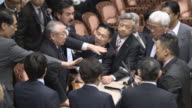 The Committee Chairperson Yoshitada Konoike surrounded by ruling party members and opposition lawmakers at the upper house in Tokyo Lawmakers...