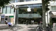 The company logo sits outside an Apple Inc store in Frankfurt Germany on Wednesday July 16 2014 Pedestrians walk past an Apple store General views...