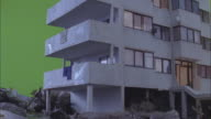 The corner of a building collapses in a flood-water simulation.