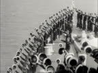 The crew onboard a British naval cruiser doff their caps and give three cheers during the Queen's inspection of the Royal Naval fleet at Spithead 1953