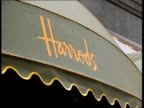 London LACMS Harrods logo on awning at store PULL OUT to Sale shoppers in queue CMS People in queue TRACK FORWARD MS Band entertaining people in...