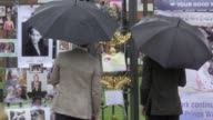 The Duke of Cambridge and Prince Harry look at tributes to Diana Princess of Wales attached to the Golden Gates of Kensington Palace London ahead of...