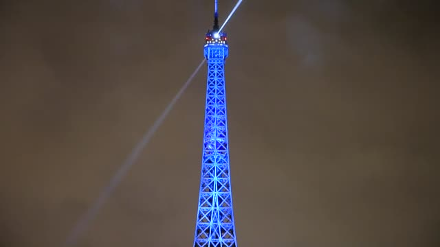 The Eiffel Tower and Ferris wheel are illuminated in the colors of the French flag to honor victims of Paris attacks on November 17 2015 in Paris...