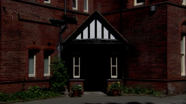 The entrance of a brick home features Tudor styling. Available in HD.