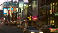 The famous Yonge St shopping district at Dundas Square early evening in Toronto Canada.  The street signs are lit at twilight.