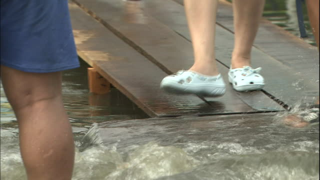 The feet of Thai shoppers cross flood water gushing across a street