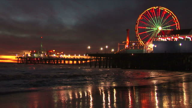 The ferris wheel at the santa monica pier with its colorful lights reflects in the surf and on the shoreline during themagical golden light after sunset