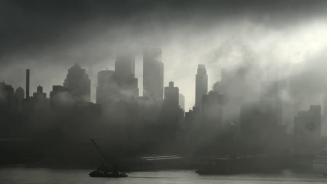 The fog slowly lifts over a dark and grey Manhattan Skyline