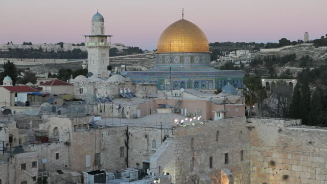 The golden roof of the Dome of the Rock contrasts with the surrounding stone buildings.