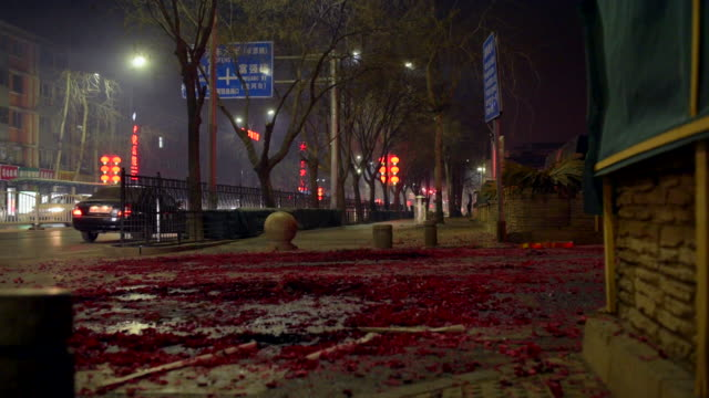 The ground is littered with pretty red paper burnt off from recently set off fireworks