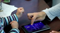 The hands of the father and son are played on the tablet