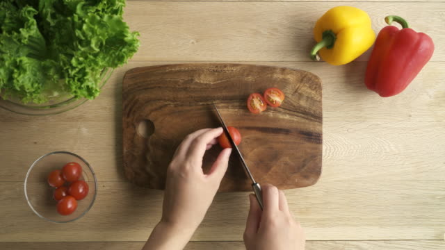 The hands of the woman cutting tomato with a knife
