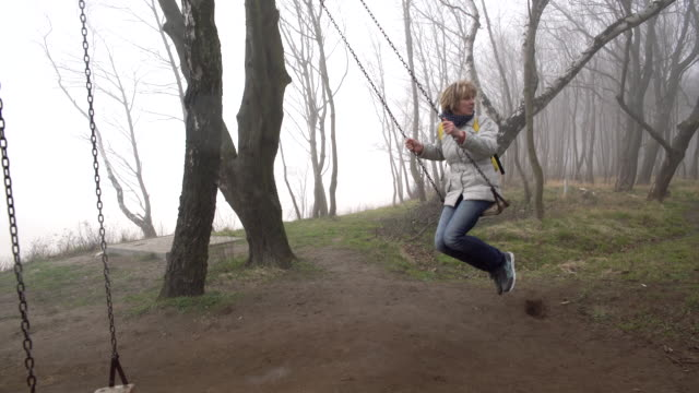 The happy beautiful active attractive 50-years-old mature woman swinging on the swings in the park