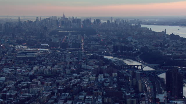 The Harlem River winds through New York City while a mauve sky hangs over the city at dusk.