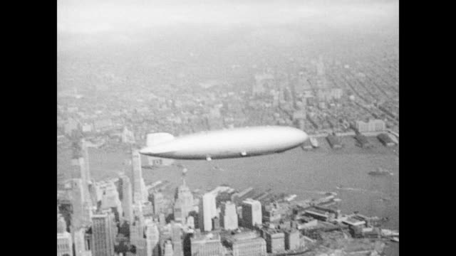 / The Hindenburg airship against the backdrop of the New York City skyline / airship flies above the countryside Hindenburg airship heads to New...