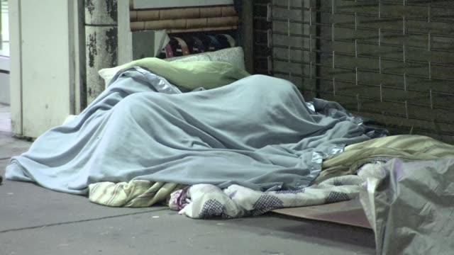 The homeless sleep in New York City as pedestrians walk by