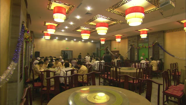 The host walks from table to table at a Chinese New Year party for restaurant employees.