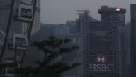 The HSBC Holdings Plc headquarters building left stand illuminated as pedestrians walk along a footbridge right at dusk in Hong Kong China on...