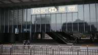 The HSBC Holdings Plc logo is displayed at the HSBC Headquarters Main Building as security guards stand beneath in Hong Kong HSBC sign on exterior of...