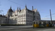 The Hungarian national flag flies outside the Hungarian Parliament Building in Budapest Hungary on Monday February 8 Tourists pose for photographs by...