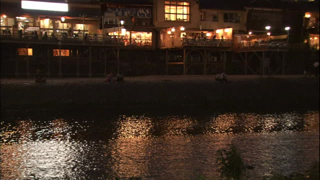 The Kamo River flows past restaurants on balconies in Kyoto, Japan.