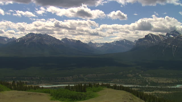 The Kootenay River winds through a Rocky Mountains valley. Available in HD.