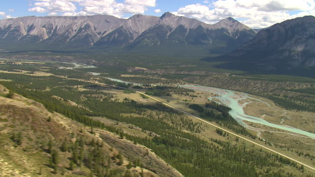 The Kootenay River winds through a valley in the Rocky Mountains range. Available in HD.
