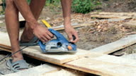 The laborer processes a wooden plank.