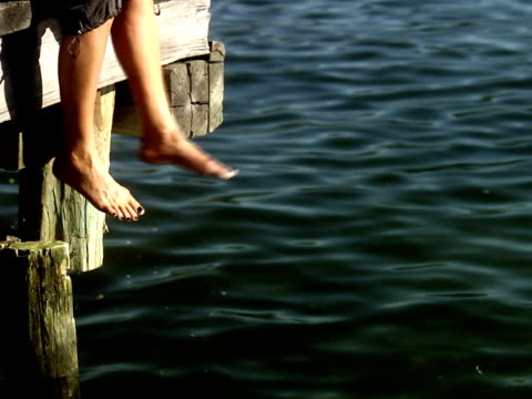 The legs of a woman sitting on a jetty by a lake Sweden.