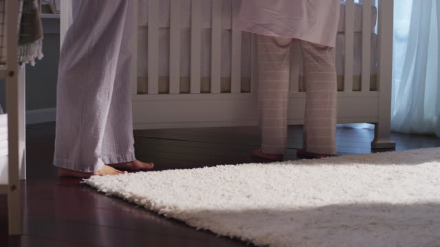 The legs of parents wearing pajamas step from a changing table to the baby's crib, then exit the nursery at night.