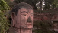 The Leshan Giant Buddha's giant head is amongst the trees. Available in HD.