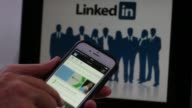 The LinkedIn Corp logo is displayed as the app opens on the screen of an Apple Inc iPhone 6 and on a laptop screen in this arranged video filmed in...