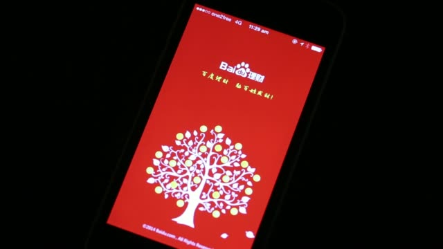 The loading page left and website for Baidulicai a unit of Baidu Inc that lets people invest in financial products are displayed on an Apple Inc...