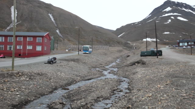 The Longyearelva River passing Longyearbyen, Spitsbergen; mountains covered by snow are seen in the back