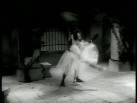 The masked stranger removes his cloak dancing ballet Pas de deux w/ in courtyard