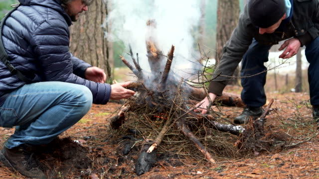 The mature 45-years-old man and his father, the active 70-years-old senior, make fire in the winter forest.