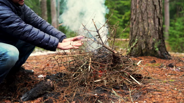 The mature 45-years-old man heating hands near by bonfire, and his father, the active 70-years-old senior, make fire in the winter forest.