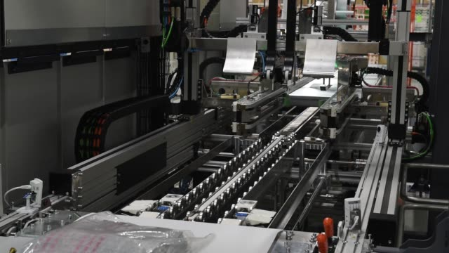 The Neopost SA CVP500 automated packing system packs a blanket in a cardboard box during a demonstration at the Yamato Holdings Co Atsugi Gateway...