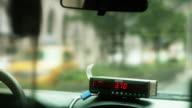 The numbers change on a fare box while a taxi drives through New York City.