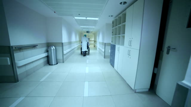 The nurse is driving a patient on wheelchair along corridor.