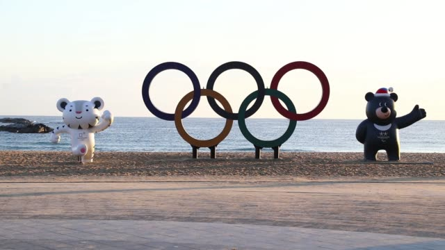 The Olympic rings and statues of the 2018 PyeongChang Winter Olympic Games mascot Soohorang left and Bandabi right stand at Gyeongpo beach near the...