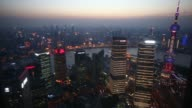 The Oriental Pearl Radio TV Tower right and commercial buildings are illuminated as they stand at dusk in Shanghai China on Tuesday April 21 2015...
