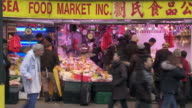 WS of the outside of a fish market in Chinatown.  Groups of people shop.
