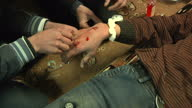 The people of Homs are under siege from Assad's forces Shows interior shots medic preparing putting drip into the hand of young man injured on...